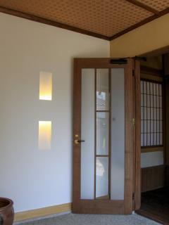 白壁のモダンな間接照明とスモークガラスの大正レトロを彷彿とさせる扉。和洋新旧の融合した玄関がこの先に...