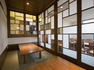 1階 座敷席|木の温もりと無機質なパターンのコントラストが面白い。