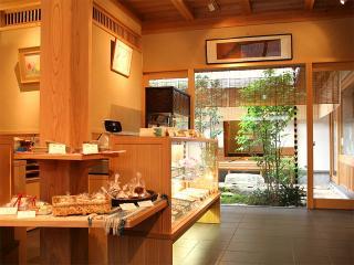 店内|風趣ある中庭を望む、新しさと懐かしさが同居した空間。奥に見える茶室では、抹茶と共にお菓子を楽し...